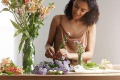 Piękna afrykańska dziewczyny kwiaciarnia ono uśmiecha się robić bukietowi w kwiatu sklepie nad biel ścianą Zdjęcia Stock