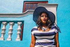 Piękna Afrykańska kobieta w błękitnej i białej pasiastej smokingowej modelacji przed tradycyjnym bo domem z błękit ścianami - Ca obrazy royalty free