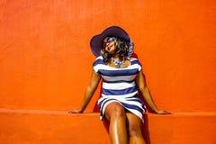 Piękna Afrykańska kobieta w błękitnej i białej pasiastej smokingowej modelacji przed tradycyjnym bo domem z pomarańcz ścianami - obrazy stock