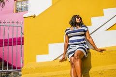Piękna Afrykańska kobieta w błękitnej i białej pasiastej smokingowej modelacji przed tradycyjnym bo stwarza ognisko domowe z kolo fotografia royalty free