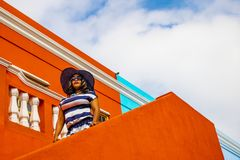 Piękna Afrykańska kobieta w błękitnej i białej pasiastej smokingowej modelacji przed tradycyjnym bo stwarza ognisko domowe z poma zdjęcia royalty free