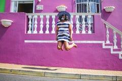 Piękna Afrykańska kobieta w błękitnym i białym pasiastym smokingowym doskakiwaniu przed tradycyjnym domem z różowymi ścianami bo, obraz royalty free