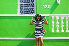 Piękna Afrykańska kobieta w bielu i błękitnym paskował smokingowy ono uśmiecha się przed tradycyjnym bo domem z zielonymi ścianam obrazy royalty free