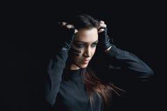 Piękna agresywna kobieta nad ciemnym tłem Ciemni i tajemniczy dziewczyny ładni stojaki w cieniu z camoflauge malują Fotografia Stock