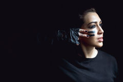 Piękna agresywna kobieta nad ciemnym tłem Ciemni i tajemniczy dziewczyny ładni stojaki w cieniu z camoflauge malują Obraz Royalty Free