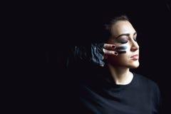 Piękna agresywna kobieta nad ciemnym tłem Ciemni i tajemniczy dziewczyny ładni stojaki w cieniu z camoflauge malują Zdjęcie Stock
