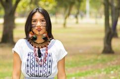 Piękna Amazonian kobieta z miejscową twarzową farbą i białą tradycyjną suknią pozuje poważnego wyrażenie dla kamery Obrazy Royalty Free