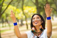 Piękna Amazonian kobieta z miejscową twarzową farbą i białą tradycyjną suknią pozuje szczęśliwie dla kamery Obrazy Royalty Free