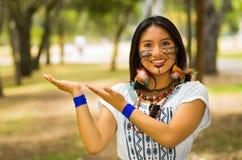 Piękna Amazonian kobieta z miejscową twarzową farbą i białą tradycyjną suknią pozuje szczęśliwie dla kamery Fotografia Stock