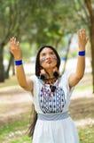 Piękna Amazonian kobieta z miejscową twarzową farbą i białą tradycyjną suknią pozuje szczęśliwie dla kamery Zdjęcia Stock