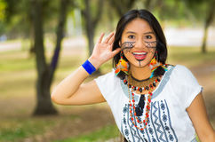 Piękna Amazonian kobieta z miejscową twarzową farbą i białą tradycyjną suknią pozuje szczęśliwie dla kamery w parku Zdjęcia Royalty Free