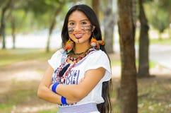 Piękna Amazonian kobieta z miejscową twarzową farbą i białą tradycyjną suknią pozuje szczęśliwie dla kamery w parku Zdjęcia Stock