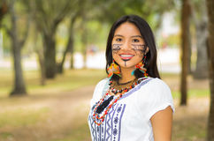 Piękna Amazonian kobieta z miejscową twarzową farbą i białą tradycyjną suknią pozuje szczęśliwie dla kamery w parku Obrazy Royalty Free