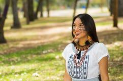 Piękna Amazonian kobieta z miejscową twarzową farbą i białą tradycyjną suknią pozuje szczęśliwie dla kamery w parku Zdjęcie Royalty Free