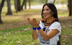 Piękna Amazonian kobieta z miejscową twarzową farbą i białą tradycyjną suknią pozuje szczęśliwie dla kamery w parku Obraz Stock