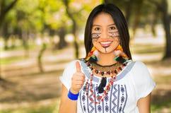 Piękna Amazonian kobieta z miejscową twarzową farbą i białą tradycyjną suknią pozuje szczęśliwie dla kamery w parku Obrazy Stock