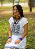Piękna Amazonian kobieta z miejscową twarzową farbą i białą tradycyjną suknią pozuje szczęśliwie dla kamery w parku Obraz Royalty Free