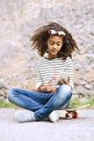 Piękna amerykanin afrykańskiego pochodzenia dziewczyna z smartphone i deskorolka Zdjęcie Stock