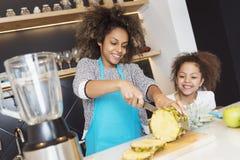 Piękna amerykanin afrykańskiego pochodzenia kobieta i jej córki tnąca owoc w kuchni fotografia royalty free