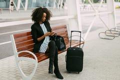 Piękna amerykanin kobieta siedzi na ławce i gawędzi przez telefonu komórkowego blisko lotniska Zdjęcie Stock