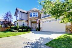 Piękna amerykanina domu powierzchowność z kamienia garażem i wierza. Zdjęcie Stock