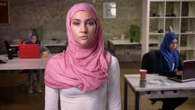 Piękna arabska kobieta jest trwanie w różowym hijab i patrzeć kamerę prosto spokojnie podczas gdy inne kobiety siedzą