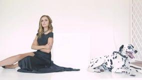 Piękna atrakcyjna dziewczyna w czarnej sukni z Dalmatyńskim psem pozuje dla fotografa w studiu zdjęcie wideo