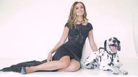 Piękna atrakcyjna dziewczyna w czarnej sukni z Dalmatyńskim psem pozuje dla fotografa w studiu zbiory