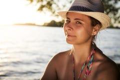 Piękna atrakcyjna garbnikująca młoda kobieta w kapeluszy spojrzeniach przy ramą na plaży na ciepłym lato wieczór przy zmierzchem Fotografia Royalty Free