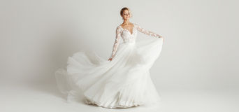 Piękna atrakcyjna panna młoda w ślubnej sukni z długą pełną spódnicą, białym tłem, tanem i uśmiechem, Obrazy Royalty Free