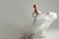 Piękna atrakcyjna panna młoda w ślubnej sukni z długą pełną spódnicą, białym tłem, tanem i uśmiechem, Obraz Royalty Free