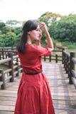 Piękna Azjatycka dziewczyna herself ubierał w tradycyjnych elementów smokingowym seansie zdjęcia royalty free