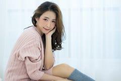 Piękna Azjatycka dziewczyna jest ubranym puloweru różowego zimno patrzeje a w domu Fotografia Royalty Free