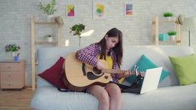 Piękna Azjatycka dziewczyna ogląda edukacyjnych wideo dalej z długie włosy w żywym pokoju nowożytna domowa studiowanie gitara zbiory