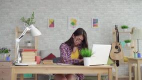 Piękna Azjatycka dziewczyna studiuje w szkłach z długie włosy w żywym pokoju z laptopem i podręcznikami w domu lub zbiory wideo