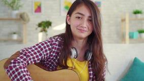 Piękna Azjatycka dziewczyna z gitarą w żywym pokoju dom, patrzeje kamery ono uśmiecha się zdjęcie wideo