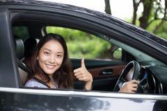 Piękna Azjatycka kobieta ono uśmiecha się i cieszy się jechać samochód na drodze zdjęcia stock