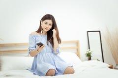 Piękna Azjatycka kobieta relaksuje w domu z hełmofonem, siedzący na łóżkowym słuchaniu muzyka od zastosowania na telefonie komórk obraz stock