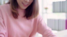 Piękna Azjatycka kobieta używa komputer lub laptop kupuje online zakupy kredytową kartą podczas gdy odzież puloweru obsiadanie na zbiory wideo