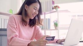 Piękna Azjatycka kobieta używa komputer lub laptop kupuje online zakupy kredytową kartą podczas gdy odzież puloweru obsiadanie na zbiory