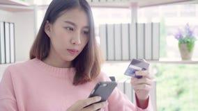 Piękna Azjatycka kobieta używa smartphone kupuje online zakupy kredytową kartą w żywym pokoju podczas gdy odzież puloweru obsiada zbiory