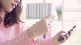 Piękna Azjatycka kobieta używa smartphone kupuje online zakupy kredytową kartą w żywym pokoju podczas gdy odzież puloweru obsiada zbiory wideo