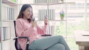 Piękna Azjatycka kobieta używa smartphone kupuje online zakupy kredytową kartą w żywym pokoju podczas gdy odzież puloweru obsiada zdjęcie wideo