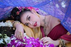 Piękna Azjatycka kobieta z tajlandzką tradycyjną suknią na orchidea przepływie fotografia royalty free
