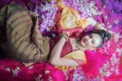 Piękna Azjatycka kobieta z tajlandzką tradycyjną suknią na orchidea przepływie zdjęcie royalty free