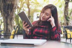 Piękna Azjatycka kobieta z uczuciem męczącym, zamyka ona oczy i mienie pastylki komputer osobisty z laptopem fotografia royalty free