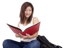 Piękna Azjatycka młoda kobieta z plecak czerwieni czytelniczą książką Fotografia Royalty Free
