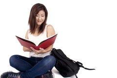Piękna Azjatycka młoda kobieta z plecak czerwieni czytelniczą książką Zdjęcie Stock