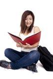 Piękna Azjatycka młoda kobieta z plecak czerwieni czytelniczą książką Obraz Royalty Free