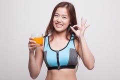 Piękna Azjatycka zdrowa dziewczyna pije soku pomarańczowego przedstawienia OK znaka Obraz Royalty Free